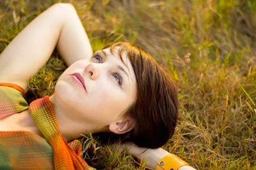 Woman in colorful scarf lying in grass looking up to the sky. Image links to abortion overview page.
