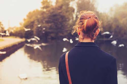 Image of woman wearing a black coat looking out over a pond.