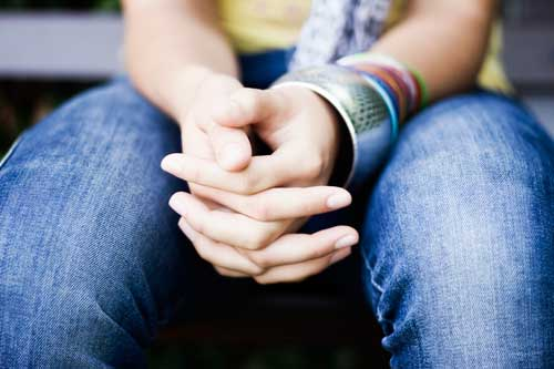 Image of young girl's hands clasped in her lap. She's wearing jeans and bracelets but you can't see her face.