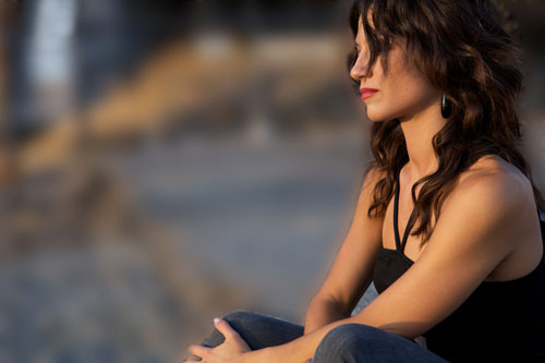 Image of a young, pensive woman sitting cross-legged with her hair in her face.