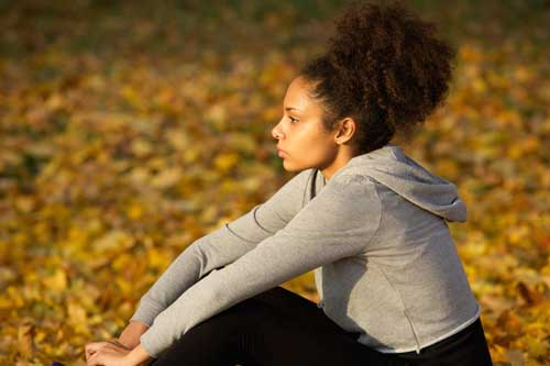 Image of a young woman wearing a hooded sweatshirt. Her hair is up and she's surrounded by fall leaves.