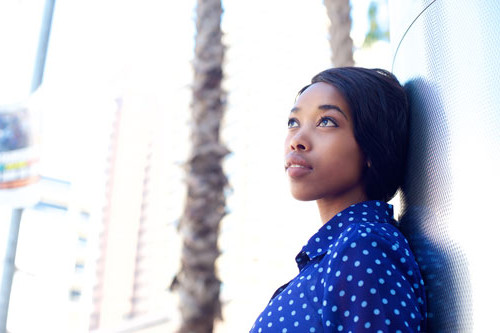 Image of young woman wearing a blue shirt with white polka-dots looking up into the distance.