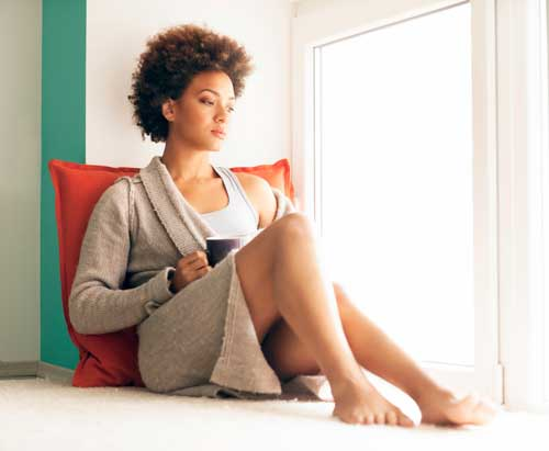Image of young woman holding a coffee mug, sitting up with her back against a red pillow while looking out a window.